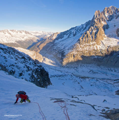 Ally on the first icefield as the sun rises over the Aiguille Verte and Drus